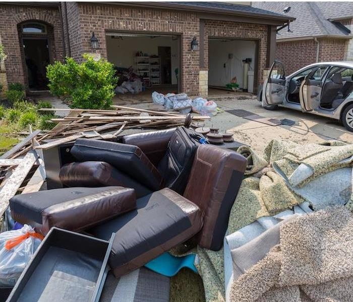 water damaged furniture, home items and ripped up carpet sitting on driveway of brick home ""