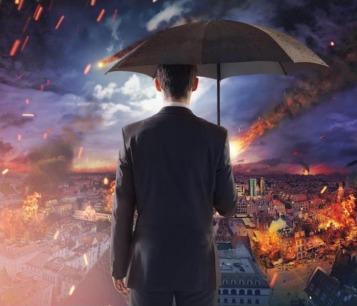 Man with Umbrella overlooking burning city